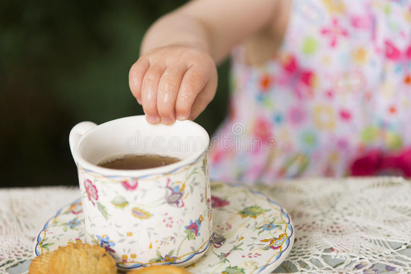 Hand of baby girl with porcelain tea cup. Hand of baby girl in colorful dress with porcelain tea cup full with tea stock photos