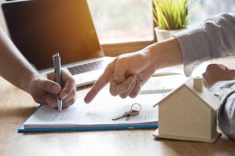 hand of bank employeer point to document and sell house after a stock photo