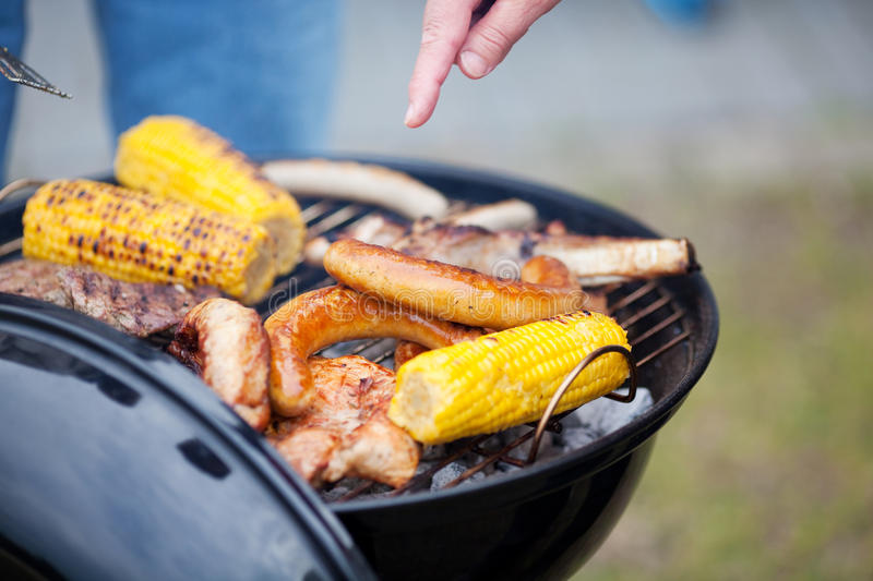 Hand Barbecuing Meat And Corn stock image