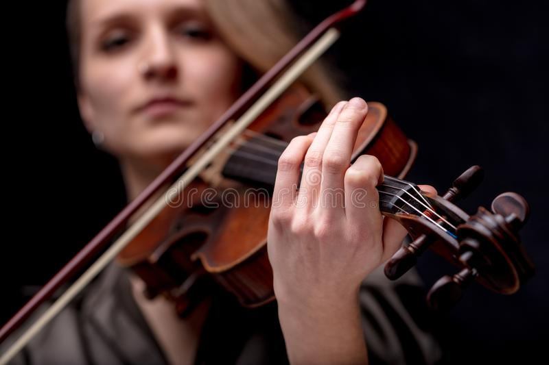Hand of a baroque violinist. Focus on the hand of a baroque violinist player on a black background, she`s very serios and determined stock image