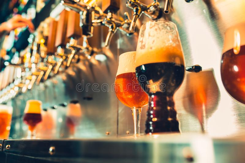 Hand of bartender pouring a large lager beer in tap. Soft, vintage instagram effect on photo royalty free stock photography