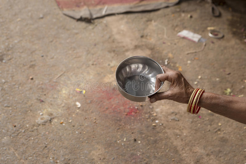 Hand of beggar. Small water dipper for begging in hand of indian beggar stock image