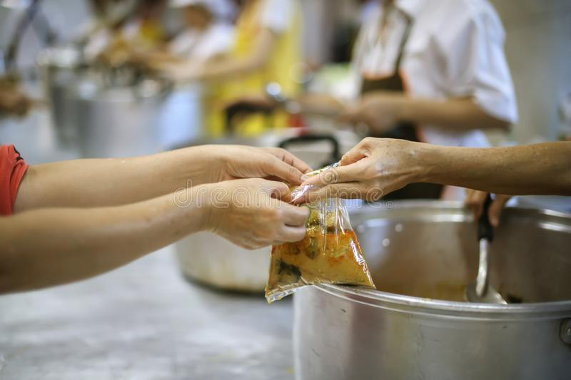 Hand begging for food from the rich`s share : the concept of hope.  stock photo