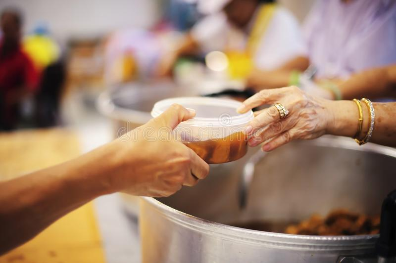 Hand begging for food from the rich`s share : the concept of hope.  stock images