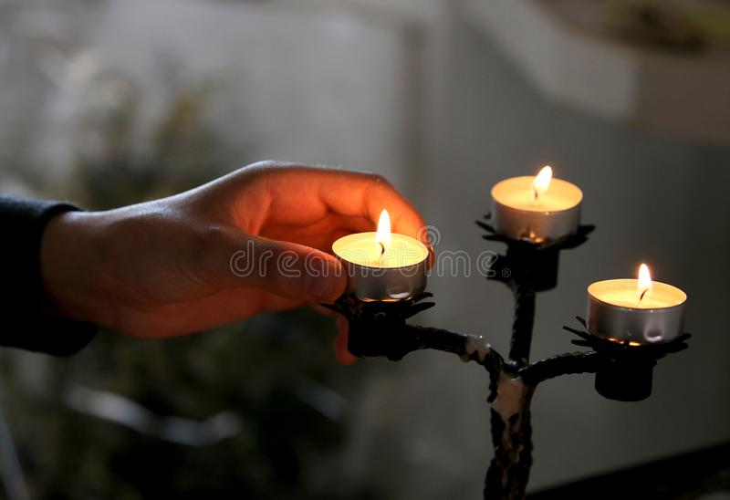 Hand of a believer who lights a candle in church stock photography