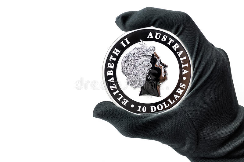 Hand in black glove holding large silver dollars coin. Hand in black glove holding large silver 10 dollars coin royalty free stock photography