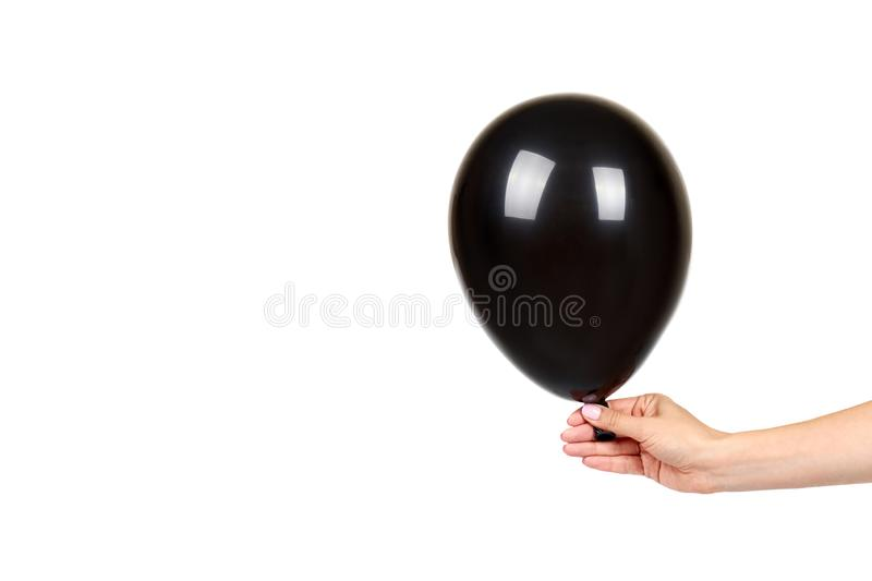Hand with black inflateble balloon, party event decoration, glossy ball. Isolated on white background. Copy space template, mockup, sphere, dark, shiny royalty free stock photos