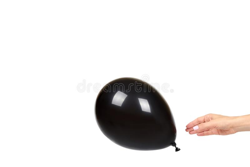 Hand with black inflateble balloon, party event decoration, glossy ball. Isolated on white background. Copy space template, mockup, sphere, dark, shiny royalty free stock photo