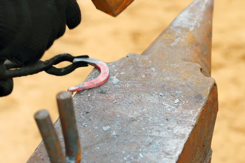Hand of blacksmith hammers hot horseshoe processing stock image