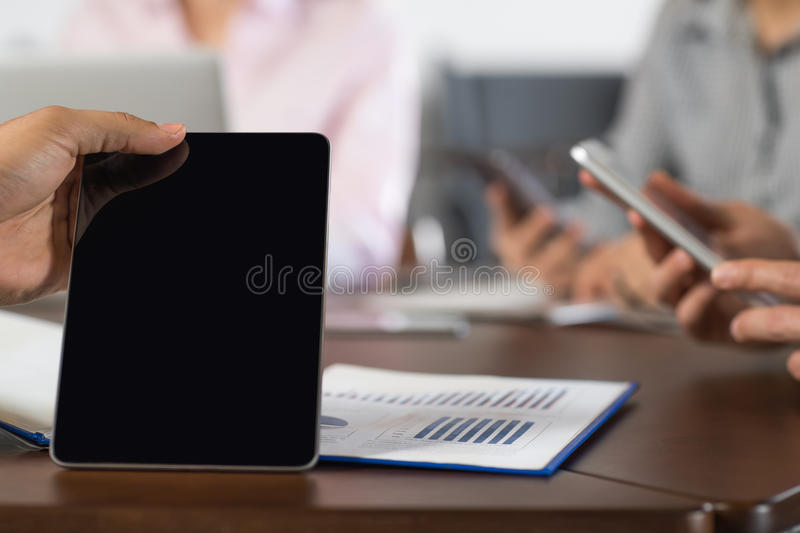 Hand Blank Black Tablet Businesspeople Group In Coworking Center Using Cell Smart Phones Team Closeup royalty free stock photo
