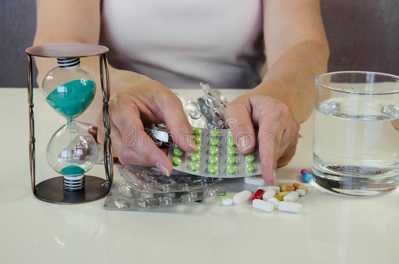 Hand with blisters of pills, glass of water and sandglass. Human hand holding blisters with medicals, glass with water and sandglass stock images