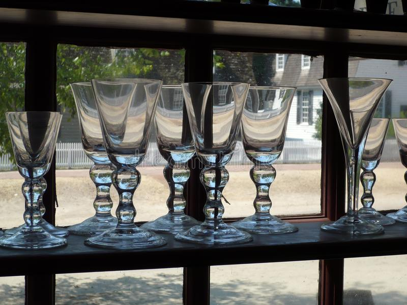 Hand blown glass goblets in window shelf royalty free stock images