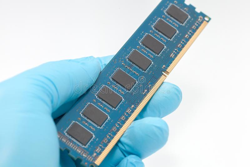 Hand in blue glove holding ram memory stock photo