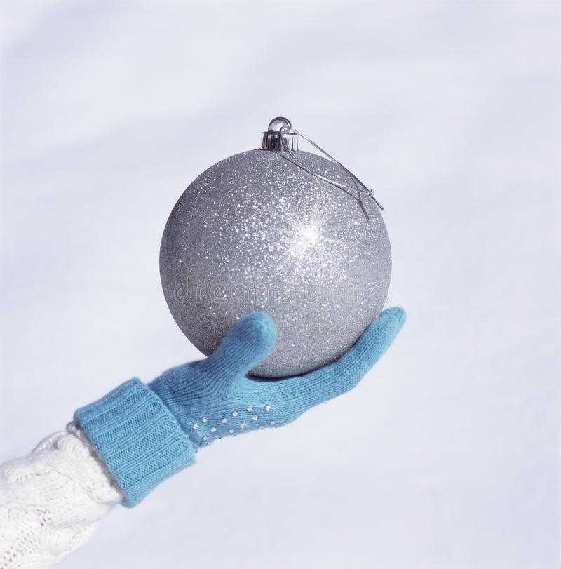 Hand with blue knit glove holding beautiful, big, sparkling, silver Christmas ornament with white snow background stock photo