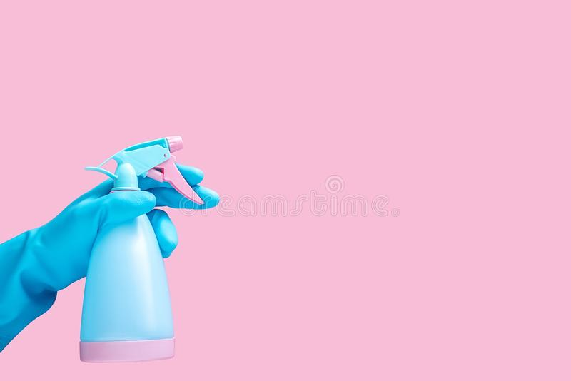 Hand in blue rubber glove holding cleaning spray bottle detergent isolated on pink background with copy space for text or logo stock photography