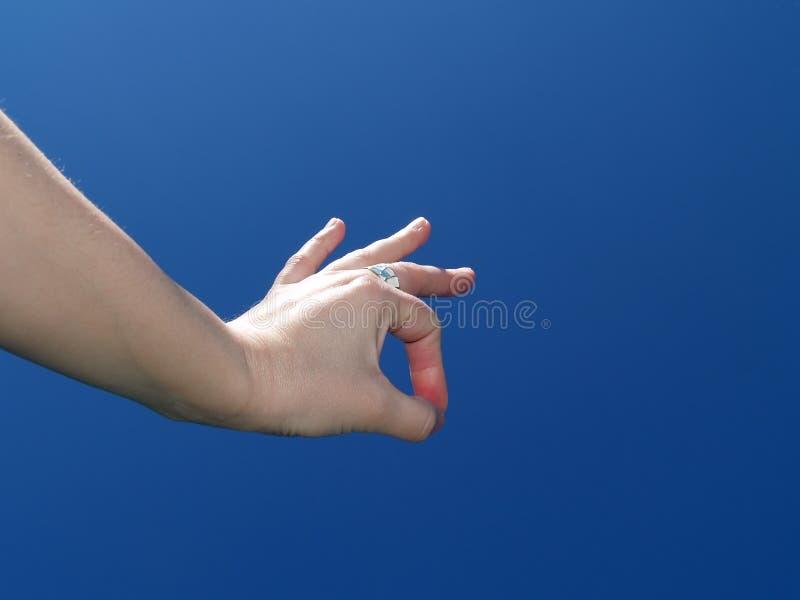 Hand on a blue sky stock photos