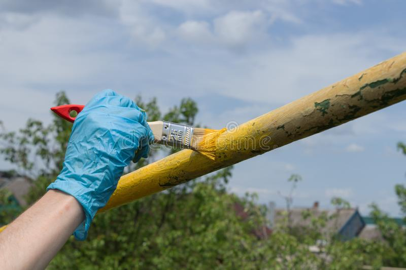 A hand in a blue working glove holds a brush and paints a metal pipe in yellow color outdoors stock photography