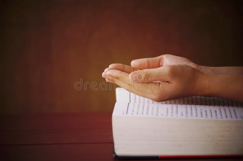 Hand on book for praying stock photos