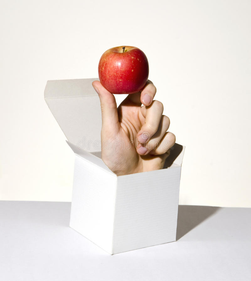 Hand in box holding apple stock image