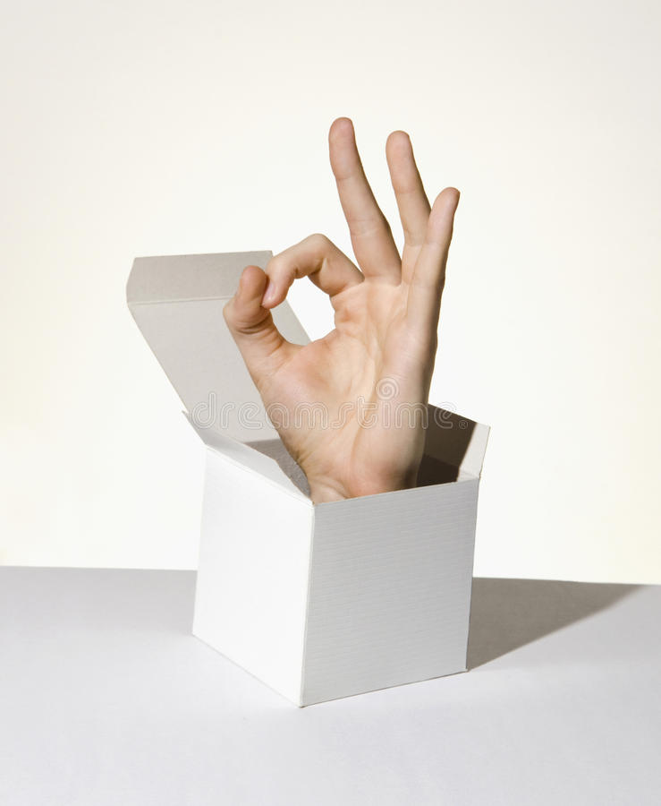 Hand in box showing aok sign. Hand popping up from box showing aok sign royalty free stock photo
