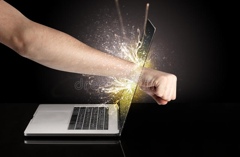 Hand boxing laptops screen. Strong arm boxing laptop screen strongly royalty free stock image
