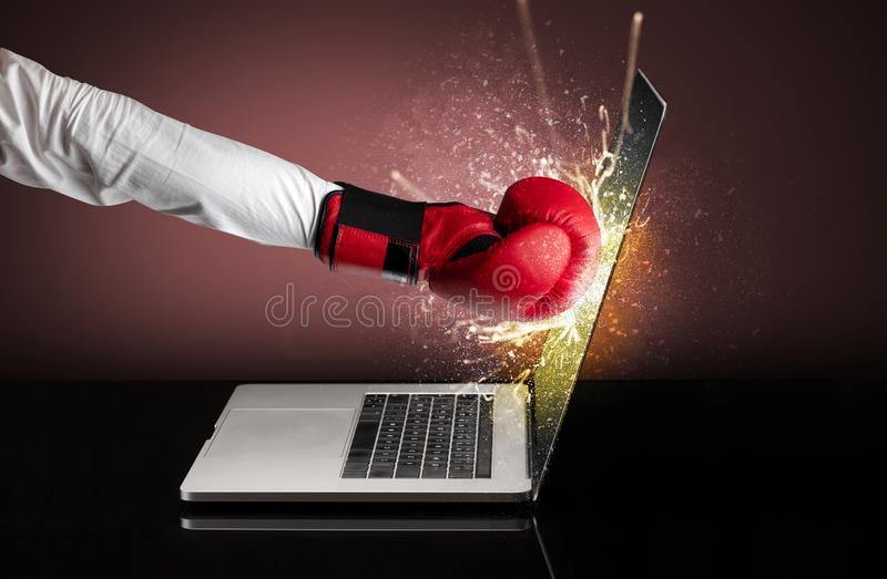Hand boxing laptops screen. Strong arm boxing laptop screen strongly royalty free stock photos