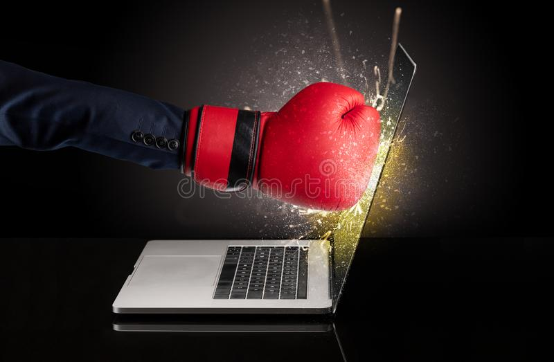Hand boxing laptops screen. Strong arm boxing laptop screen strongly royalty free stock photography
