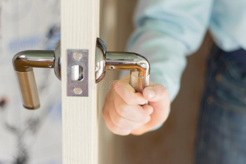 The hand of the boy holding the door handle opening it royalty free stock photo