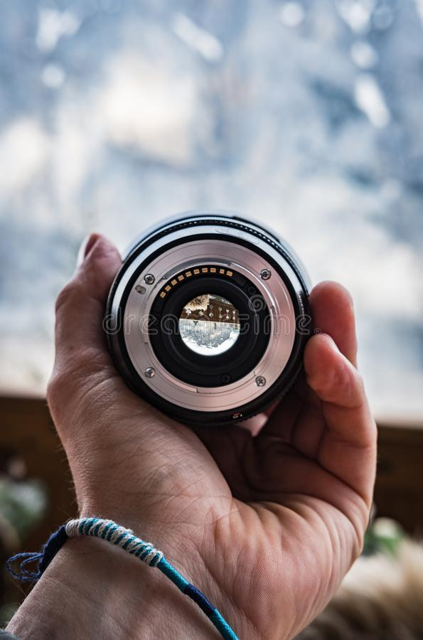 Hand with a bracelet holding a large camera lens royalty free stock photos