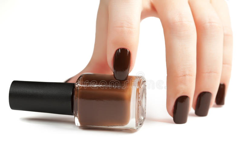 Hand with brown manicure and nail polish bottle royalty free stock photography