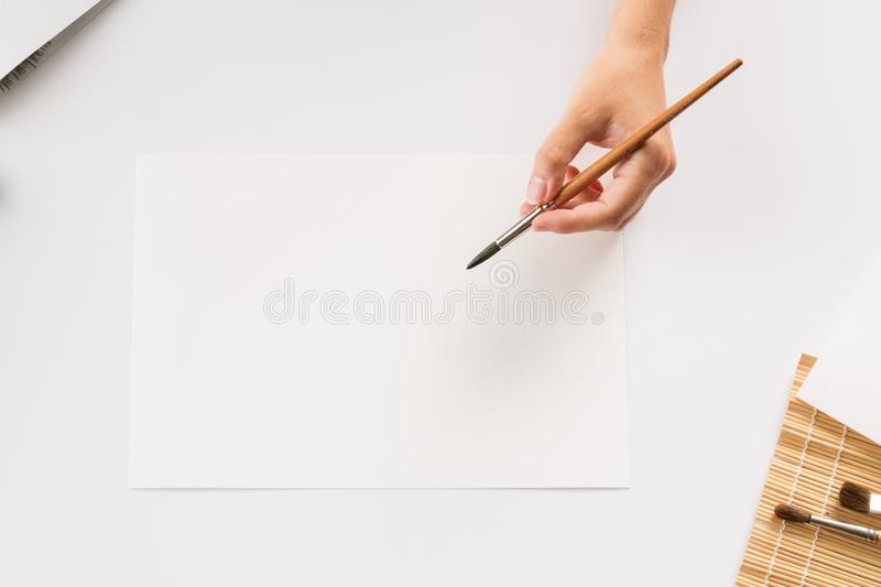 Hand with a brush draws on white paper background stock photo