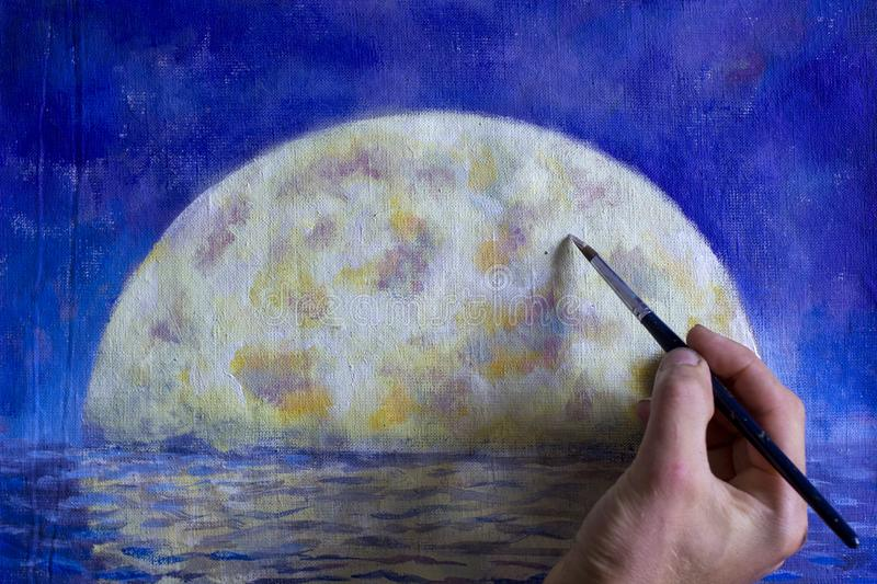 Hand with brush paint a orange big moon in blue, reflection of moon in ocean, sea, water. Artist painter man drawing with brush night big moon in water royalty free stock photo