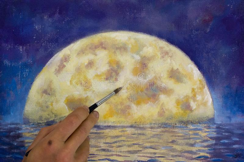 Hand with brush paint a orange big moon in blue, reflection of moon in ocean, sea, water. Artist painter man drawing with brush night big moon in water stock photography