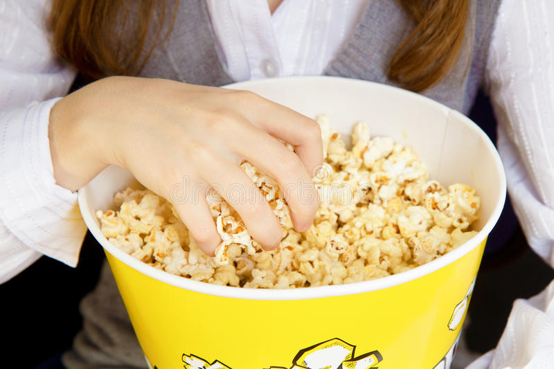 Hand in a bucket of popcorn royalty free stock photos