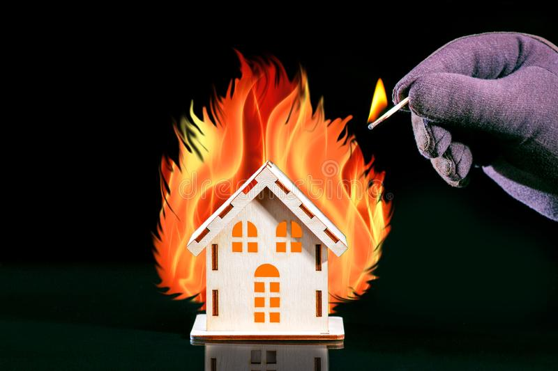 Hand with a burning match sets fire to the house model. Fire safety concept. House With A Big Fire. Hand with a burning match sets fire to the house model. Fire stock image