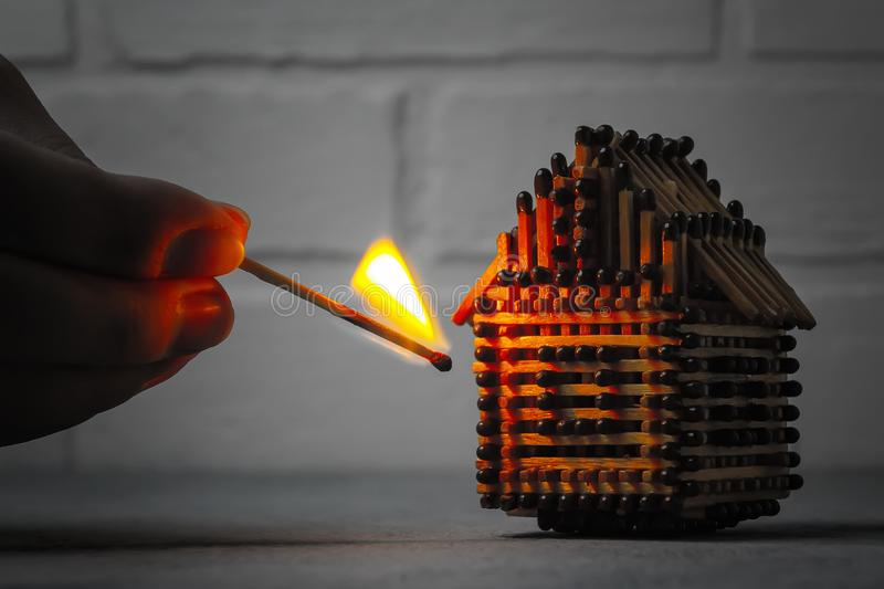 Hand with a burning match sets fire to the house model of matches, risk, property Insurance protection or ignition of combustible royalty free stock image