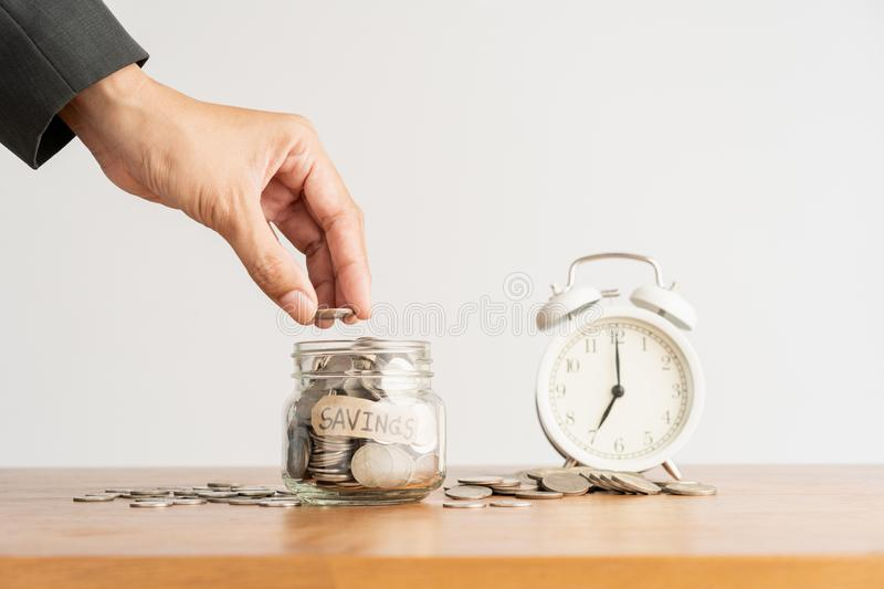 Hand of  business man put a coin in a glass bottle, a pile of coins and a retro white alarm clock on a brown wooden table, stock photos