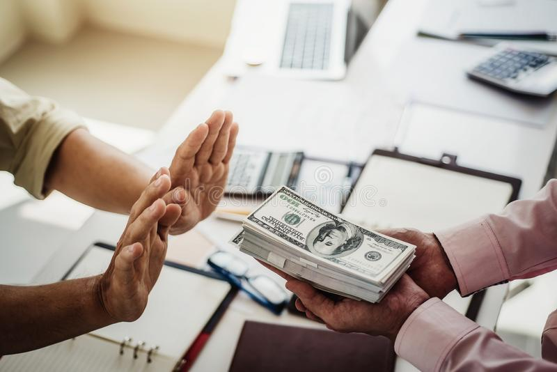 Hand of business man refuse receive money for taking bribe while making contract. bribery and corruption concept royalty free stock images