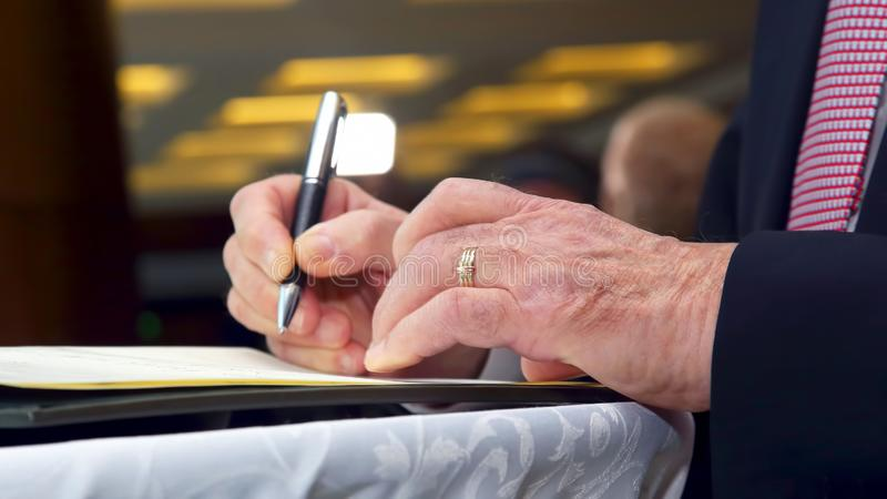 Hand of a business man signs an important document with a pen. The hand of a business man signs an important document with a pen royalty free stock photo