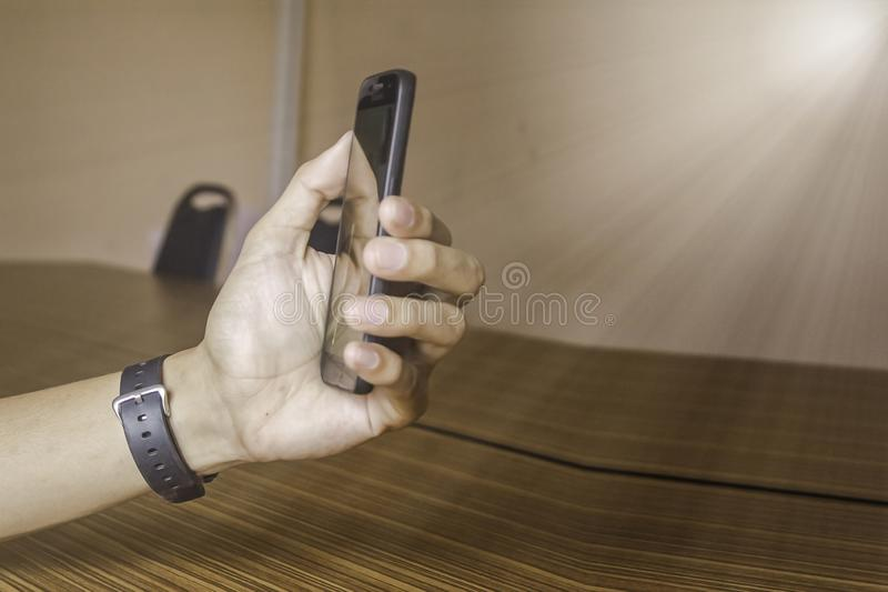 Hand business man with watch and holding smart phone with finger. To touch screen show tablet stock photography