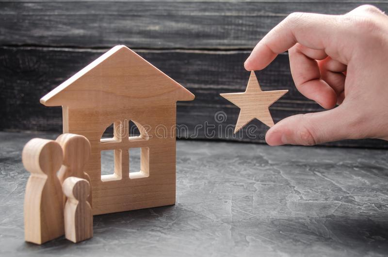 A hand in a business suit brings a star to the wooden house. The family stands near the house. A badge, the best house. Excellent. Quality and high rating stock photo