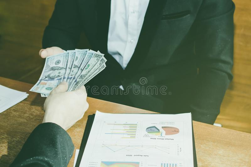 Hand businessman counting money buying stock company Real estate Success in the future,workers each receive an annual bonus. With sunset background royalty free stock images