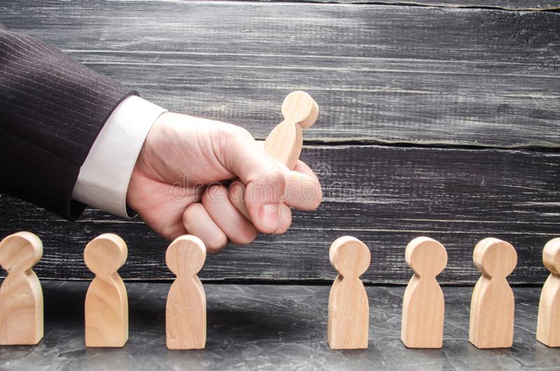 The hand of a businessman grabs a wooden figure of a man from a number of workers. The concept of business management. Human resources. Specialists, career stock image