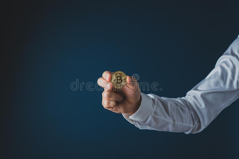 Hand of a businessman holding a golden coin of crypto currency. Bitcoin. Over navy blue background stock photography