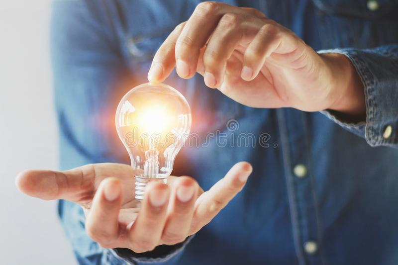 hand businessman holding lightbulb and touch. concept saving ene royalty free stock image