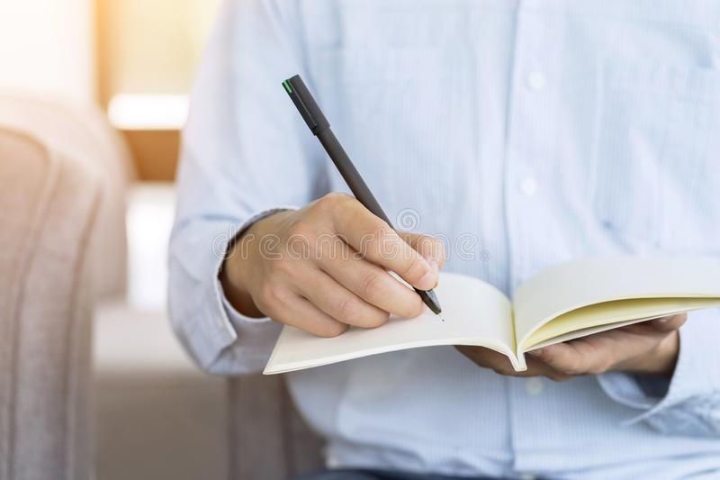 Hand of businessman holding pen and notebook, Writing something idea on note or check list royalty free stock image