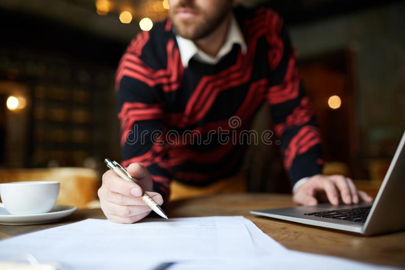 Man with pen. Hand of businessman holding pen over sheet of paper between cup of tea and laptop royalty free stock photo