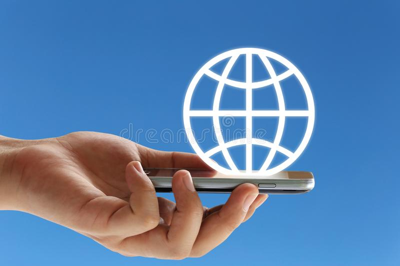hand of a businessman holding a smartphone and a world logo on b royalty free stock photography