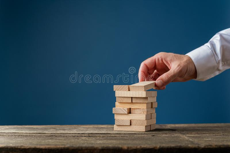 Hand of a businessman making a stack of wooden pegs royalty free stock photo