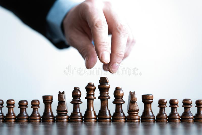 Hand of businessman moving chess figure in competition success play. strategy, management or leadership concept. stock photo